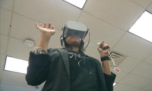 A woman wearing VR goggles holding up her hands